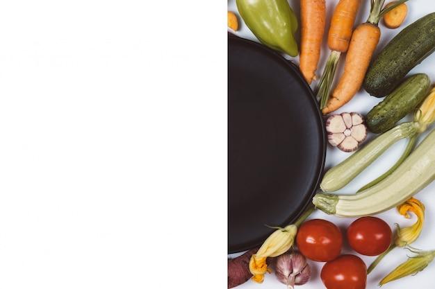 トマト、タマネギ、キュウリ、ニンジン、ニンニク、ズッキーニ、白い背景に黒のプレート。
