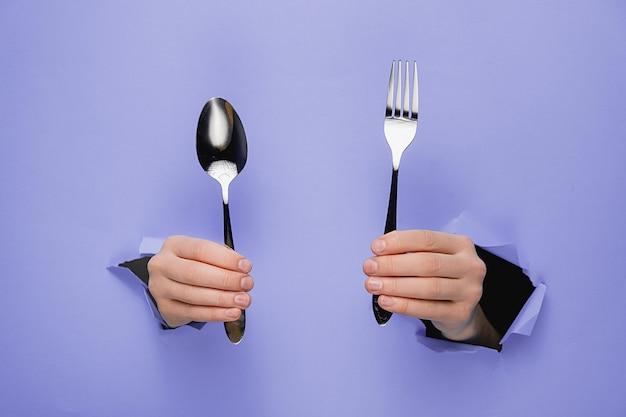 引き裂かれた紫色の紙の壁を通してスプーンとフォークを保持している女性の手のクローズアップ。