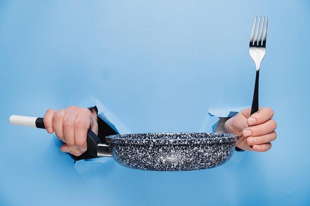 破れた紙の青い背景を通してフライパンとフォークを保持している女性の手のクローズアップ。