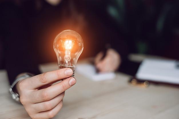 会計と創造のための電球を保持している女性の手。