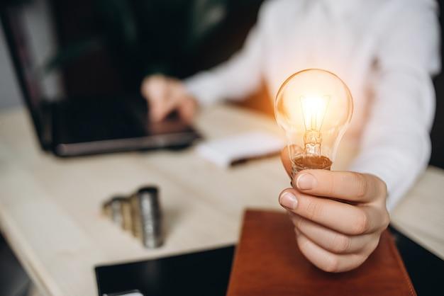 ビジネスの女性はオフィスで机の上の電球を保持しているとコンピューターで動作します。
