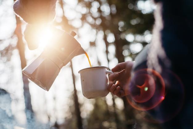Открытый выстрел молодой женщины наливает себе горячий напиток в горах рядом с костром во время заката.