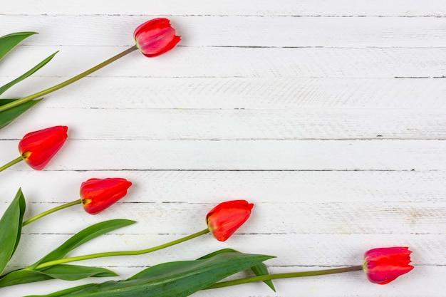 白い木製の背景に赤いチューリップの花の花束