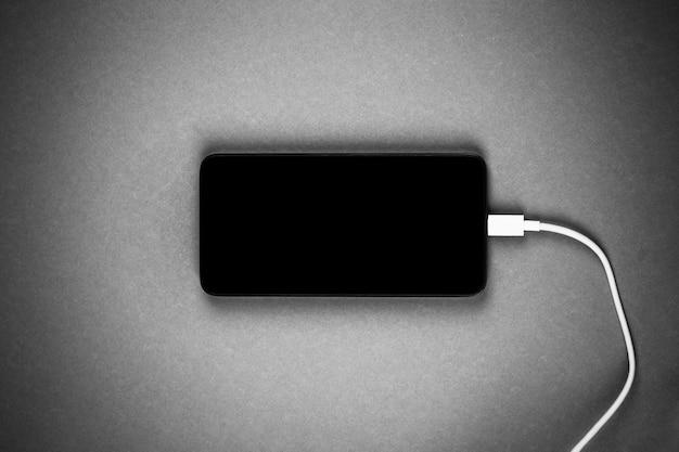 Новый смартфон с черным экраном с белым проводом от зарядного устройства