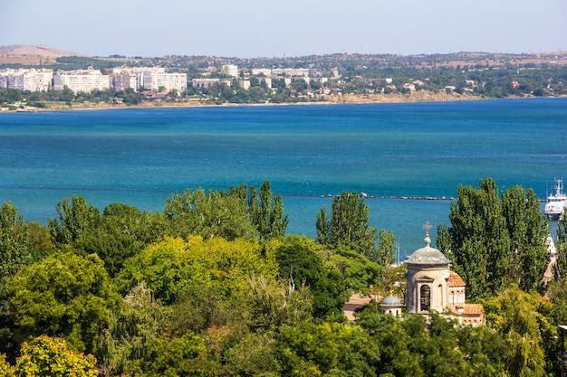 Красивый летний пейзаж с видом на море и древний византийский храм среди зеленой листвы деревьев