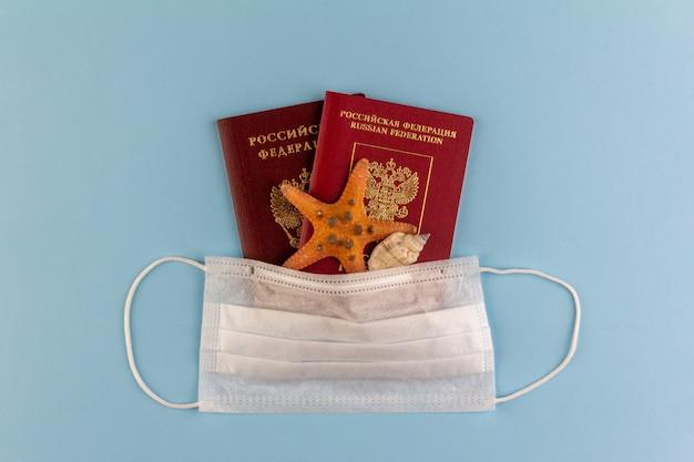 Два российских паспорта, морская звезда и морская ракушка под одноразовой медицинской маской на синем