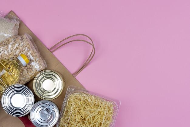 Бумажный пакет с кризисной подачей продовольствия на период карантинной изоляции на розовом фоне