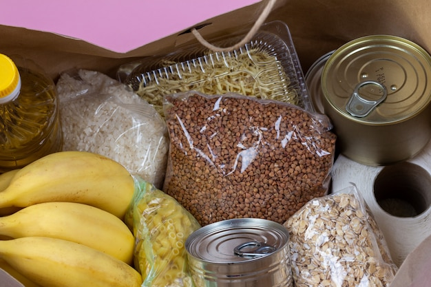 Бумажный пакет с кризисной подачей продовольствия на период карантинной изоляции на розовом фоне, макароны, гречка, консервы, рис, бананы крупным планом.