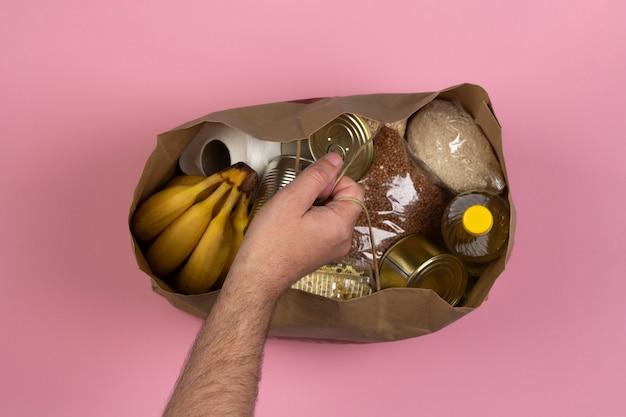 Бумажный пакет с кризисным снабжением продовольствием на время карантинной изоляции на розовом фоне, макароны, гречка, консервы, рис, бананы в мужской руке крупным планом. концепция доставки еды, пожертвования.