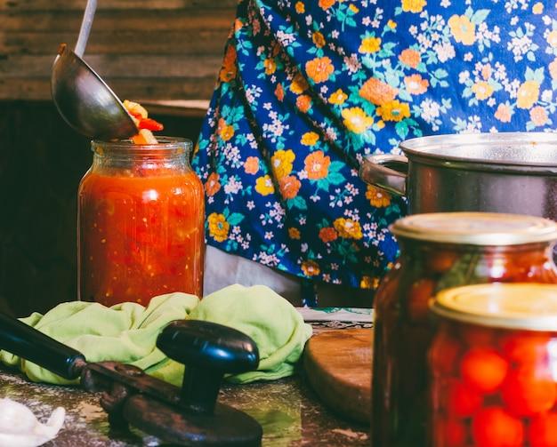 Человек в цветном фартуке забивает помидоры и соус лечо в стеклянных банках на ферме