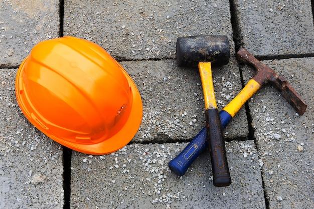 オレンジ色の建設帽子と灰色の瓦礫コンクリートブロックのハンマー。クローズアップ、上面図