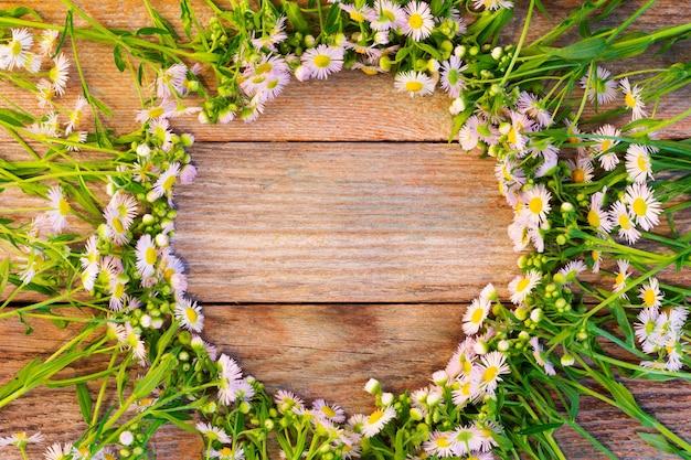 木製ビンテージ背景にカモミールのラウンドフレーム