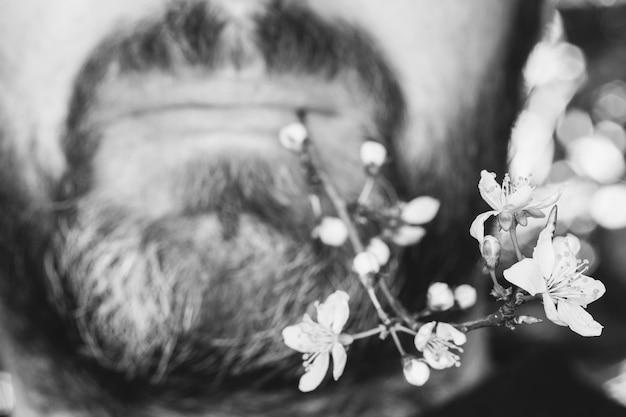 彼の唇に開花小枝を持つひげと口ひげを持つ男性の顔
