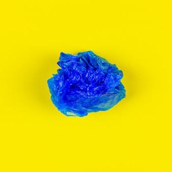 Голубой полиэтиленовый пакет на желтой предпосылке, взгляд сверху.