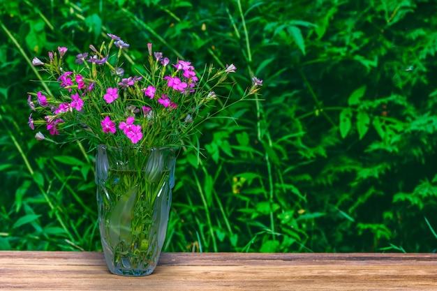 コピースペースを持つ緑の自然の背景にガラスの花瓶にカーネーションの花束