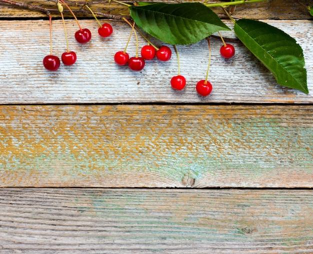 古い納屋ボードの背景に赤い熟したチェリーと枝