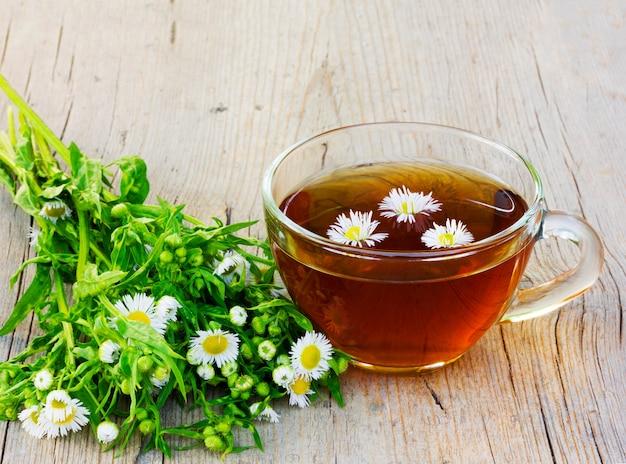 カモミールの花と亀裂の古い木製のテーブルの上のカモミールとお茶の素敵なカップをクローズアップ