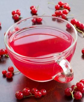 絞りたての赤いジュース、および木製のテーブルのクローズアップの赤いスグリの束