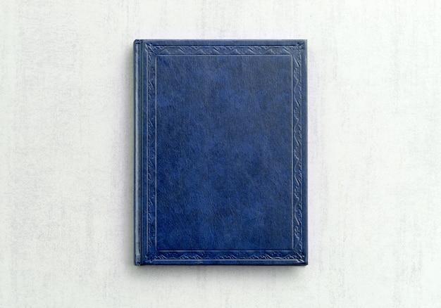 Макет книги синего цвета на сером фоне крупным планом, вид сверху