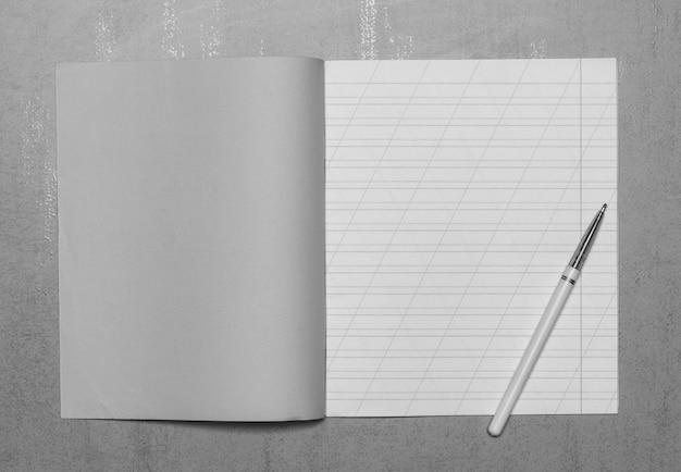 Открытая школьная тетрадь в узкой линии с косой чертой для изучения макета правописания с копией пространства и шариковой ручкой на сером фоне, вид сверху, черно-белая фотография
