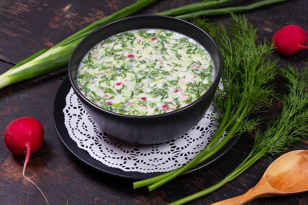 Русский летний холодный суп окрошка из зелени, овощей, кваса и кефира на черном деревянном столе