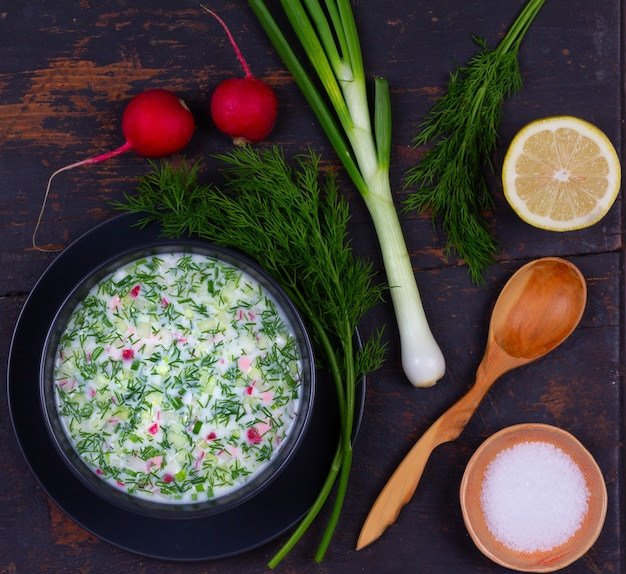 Русский летний холодный суп окрошка из овощей, кваса и кефира с зеленью на черном столе