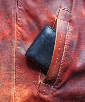 Черный кошелек, торчащий из кармана красной куртки из кожи