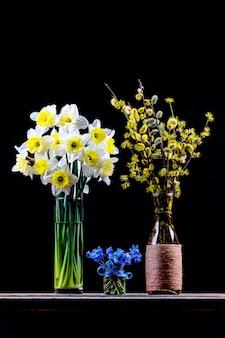 ヤナギとハナミズキの花瓶の開花枝の花束、水仙の花の花束と花瓶のブルーベルの花の花束
