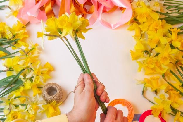 男の花屋は水仙の花の花束を作る