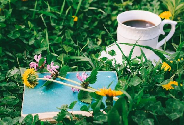 古い本と夏または春の朝の緑の牧草地でホットコーヒーのカップ