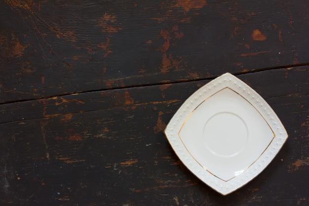古い黒い木製テーブルの上の白いセラミック正方形受け皿。
