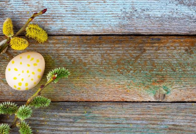 コピースペースを持つ木製のレトロな背景に黄色のドットのパターンで咲く柳の小枝とイースターエッグのイースター組成。トップビューのクローズアップ。