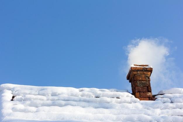 雪に覆われた屋上のレンガの煙突から煙