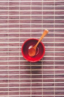 Деревянная ложка в пустой красной чашке на коричневой бамбуковой циновке