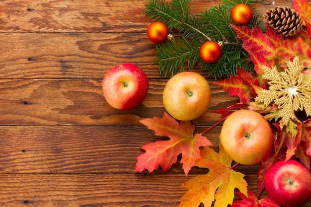 Спелые яблоки, разноцветные кленовые листья, еловая ветка с елочными украшениями и шишка на деревянной доске