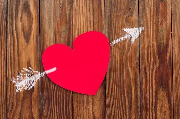 バレンタインの赤い紙のハートのバレンタインカードは、木の板にチョークで描かれた矢印で穴を開けられました。