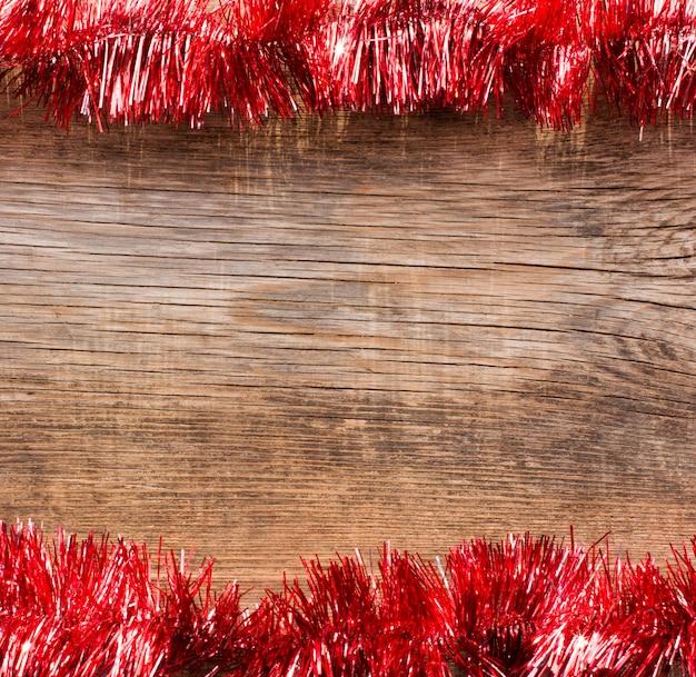 Старые деревянные доски обрамленные красной мишурой. новый год, новогодний фон с пространством для текста.