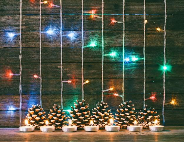 Праздничный новый год и рождество концепция. разноцветные рождественские огни гирлянды, еловые шишки и свечи на фоне старых сарайных досок