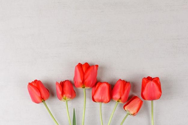 コピースペースと灰色の背景に赤いチューリップの花束。