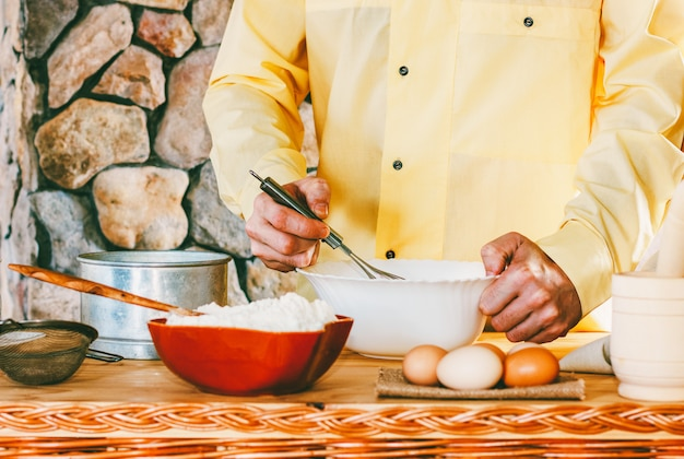 黄色の服を着た男性料理人が泡立て器で泡立て器を泡立て器、セレクティブフォーカス