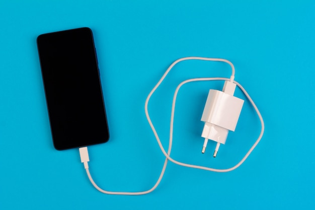 Смартфон с черным экраном и белым зарядным проводом