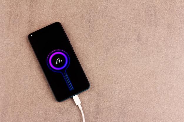 Смартфон с индикатором заряда аккумулятора на экране с белым зарядным проводом