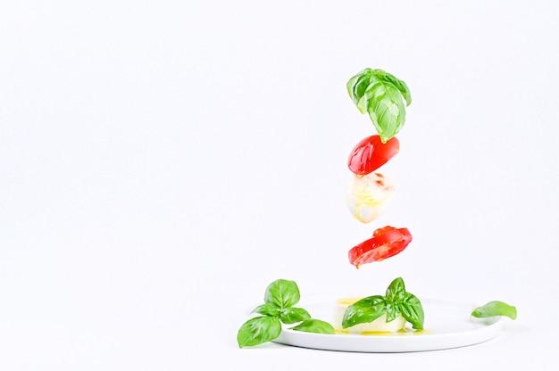 Летающий салат в кадре. традиционный итальянский салат капрезе. помидоры, моцарелла, базилик, оливковое масло