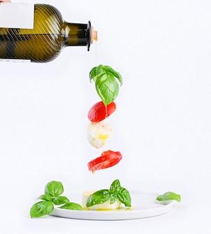 Женская рука с бутылкой масла и летающий салат в кадре. традиционный итальянский салат капрезе. помидоры, моцарелла, базилик, оливковое масло
