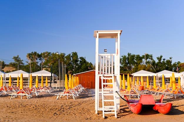 ビーチの階段と木製の救助箱。砂浜とサンラウンジャー。夜明けと海のまぶしさ。旅行と観光。