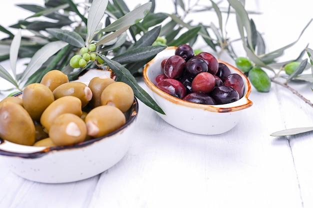 伝統的な前菜、ギリシャ料理の緑と赤のオリーブ。白いウッドの背景。オリーブの新鮮な枝。コピースペース