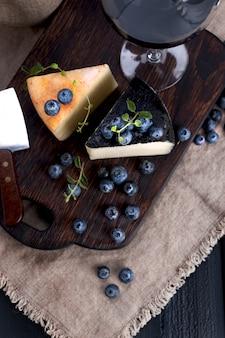 ペコリーノチーズとブルーベリー、木の板とワインのグラス