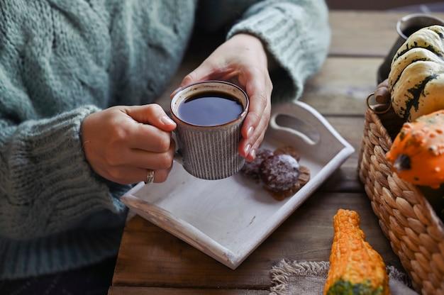 秋、カボチャ、木製テーブルの上のコーヒーの熱い蒸しカップ。季節の朝のコーヒー、ビスケットシナモンクッキー、日曜日はリラックス。鶏のカップとセーターの女の子