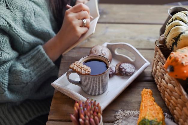 秋、カボチャ、木製テーブルの上のコーヒーの熱い蒸しカップ。季節の朝のコーヒー、日曜日のリラックス、静物。当日の計画
