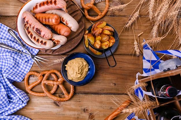オクトーバーフェストのお祝いに、マスタード付きの伝統的なバイエルングリルソーセージ。木製および国民の食糧。上面図